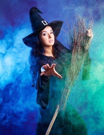 angry sexy young brunette witch with a broom stretching her hand to us, isolated against white background photo