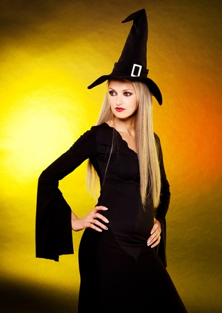 sexy young blond witch, against yellow background photo