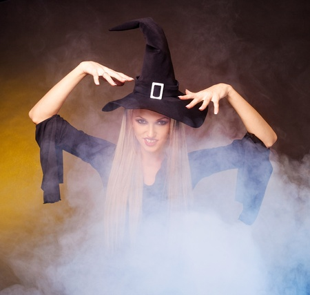 spells: angry young blond witch with  clouds of blue smoke around her,against black and yellow background