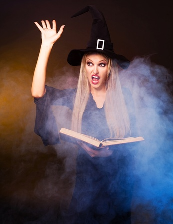 spell: angry  blond witch with a book and her hands and clouds of blue smoke around her conjuring, against black and yellow background
