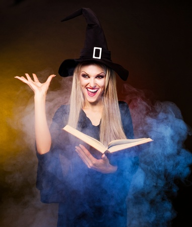 conjuring: angry  blond witch with a book and her hands and clouds of blue smoke around her conjuring, against black and yellow background