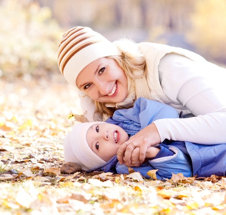 outsides: happy young mother and her son spending time outdoor in the autumn park  (focus on the woman) Stock Photo