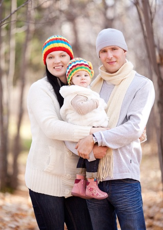 happy young family with their daughter spending time outdoor in the autumn park (focus on the baby) Stock Photo - 10794182