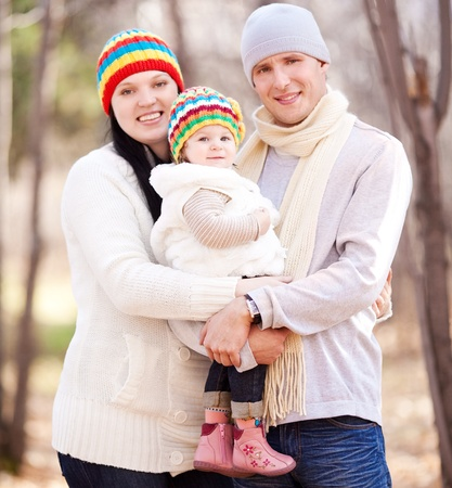happy young family with their daughter spending time outdoor in the autumn park (focus on the baby) Stock Photo - 10794766