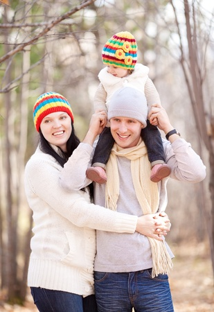 happy young family with their daughter spending time outdoor in the autumn park (focus on the baby) Stock Photo - 10794785