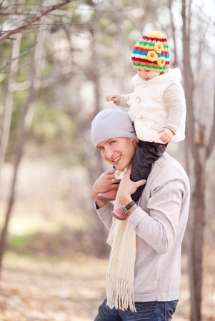 happy young father with his daughter spending time outdoor in the autumn park (focus on the man) Stock Photo - 10794755