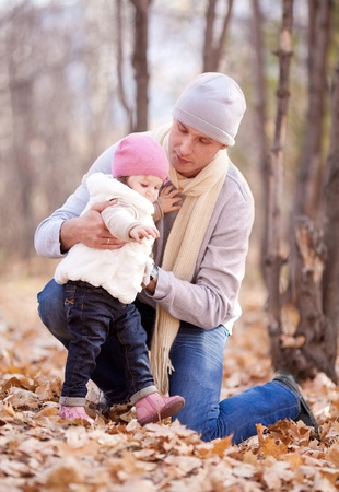 happy young father with his daughter spending time outdoor in the autumn park and teahcing her to walk Stock Photo - 10794781