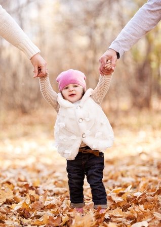 parents: happy family with their baby spending time outdoor in the autumn park  and teaching her walking