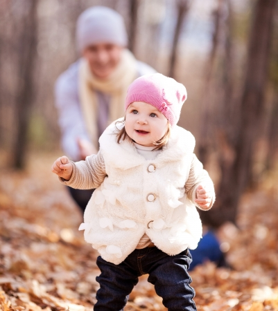 happy young father playing with his daughter  in the autumn park (focus on the child, the man is at a distance, the man is at a distance) Stock Photo - 10794761