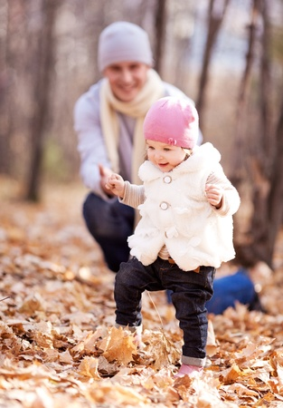 happy young father playing with his daughter  in the autumn park (focus on the child, the man is at a distance) photo