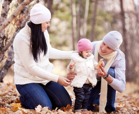 happy young family with their daughter spending time outdoor in the autumn park (focus on the woman) photo