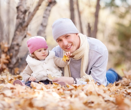 happy young father with his daughter spending time outdoor in the autumn park (focus on the man) Stock Photo - 10794749
