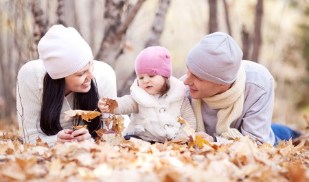 happy young family with their daughter spending time outdoor in the autumn park (focus on the woman) Stock Photo - 10794750