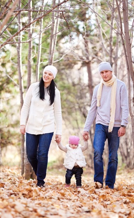happy young family with their daughter spending time outdoor in the autumn park (focus on the man and woman) photo