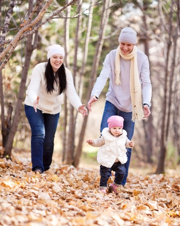 happy young family with their daughter spending time outdoor in the autumn park (focus on the man and child) Stock Photo - 10794767