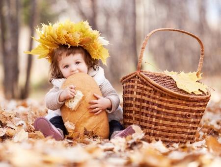 буханка: милая девочка, имея пикник, сидя на гра в осеннем парке и ел батон
