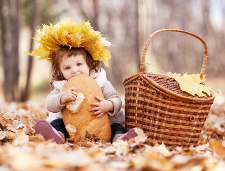 fall fun: cute baby girl having a picnic, sitting on the gras in the autumn park and eating a long loaf Stock Photo