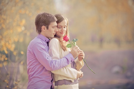 tender passion: low contrast image of a happy young couple spending time outdoor in the autumn park (focus on the man)