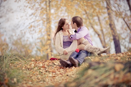 lovers park: low contrast image of a happy romantic young couple spending time outdoor in the autumn park   Stock Photo