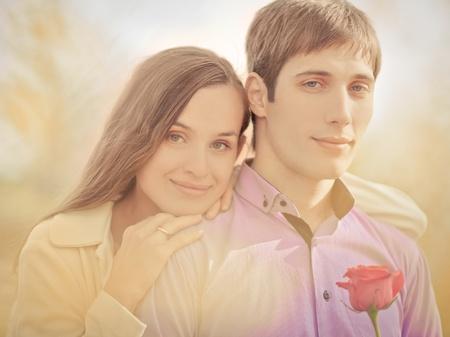 jovenes enamorados: imágenes de bajo contraste de una feliz pareja romántica pasar tiempo al aire libre en el Parque de otoño (foco en el hombre) Foto de archivo