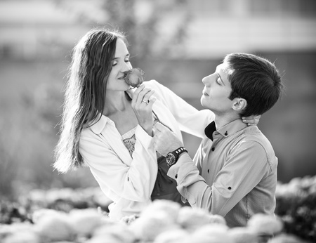 black and white image of a happy romantic young couple spending time outdoor in the autumn park  (focus on the man) photo