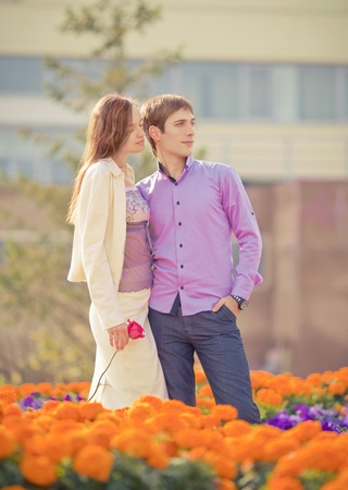 low contrast image of a happy romantic young couple spending time outdoor in the autumn park  (focus on the man) photo