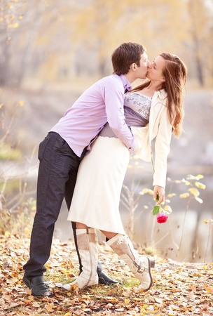 romantic kiss: low contrast image of a happy romantic young couple spending time outdoor in the autumn park