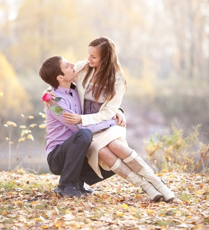 young love: happy romantic young couple spending time outdoor in the autumn park   Stock Photo