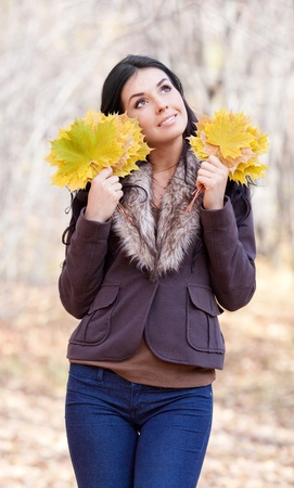 outsides: beautiful young brunette woman with maple leaves in her hands,  spending time in the autumn park