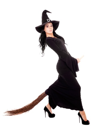 sexy young brunette witch with a broom, isolated against white background photo