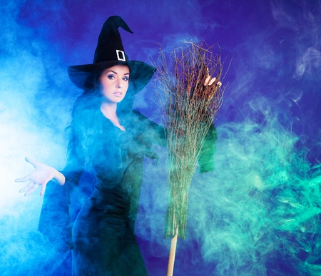 wicked woman: sexy young brunette witch with a broom stretching her hand to us, against purple background