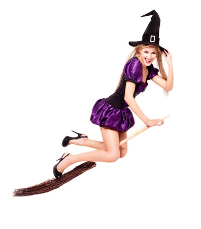 pretty sexy young blond witch flying on the broom, isolated against white background photo