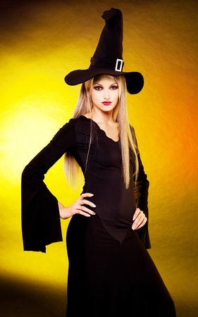sexy young blond witch, against yellow studio background photo