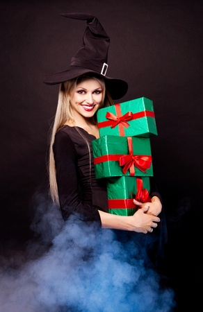 sexy smiling young blond witch with  presents in her hands, against black background photo
