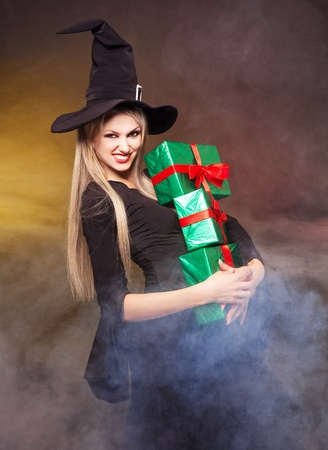 young blond witch with  presents in her hands, against black background photo