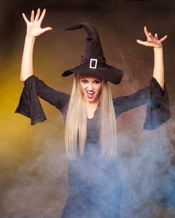 angry young blond witch with  clouds of blue smoke around her,against black and yellow background photo