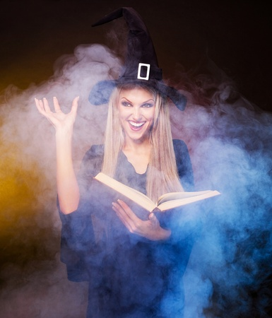 conjuring: blond witch with a book and her hands and clouds of blue smoke around her conjuring, against black and yellow background Stock Photo