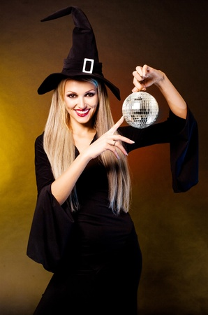 witch hat: sexy young blond witch with a disco ball, against black and yellow studio background Stock Photo