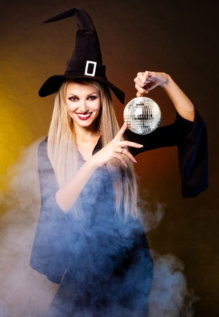 sexy young blond witch with a disco ball, against black and yellow studio background photo