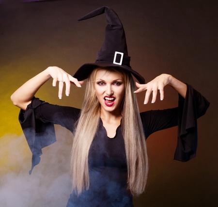 brujas sexis: enojado joven bruja rubia con nubes de humo a su alrededor, sobre fondo negro y amarillo azul Foto de archivo