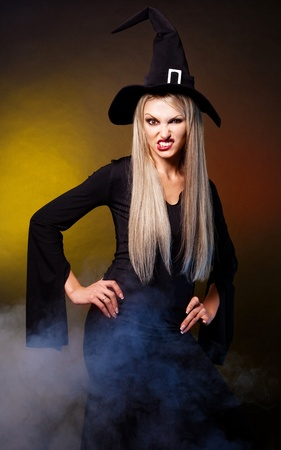 angry young blond witch with  clouds of blue smoke around her,against black background photo