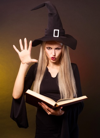 magician: angry  blond witch with a book conjuring, against black and yellow background Stock Photo