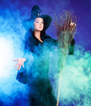 wicked: sexy young brunette witch with a broom stretching her hand to us, against purple background