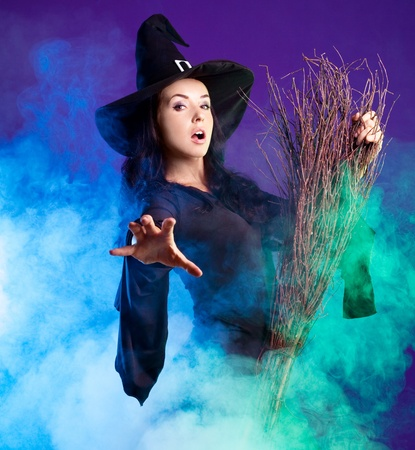 spells: sexy young brunette witch with a broom stretching her hand to us, against purple background