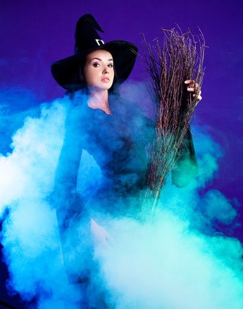 sexy young brunette witch with a broom and foam around her, isolated against white background photo