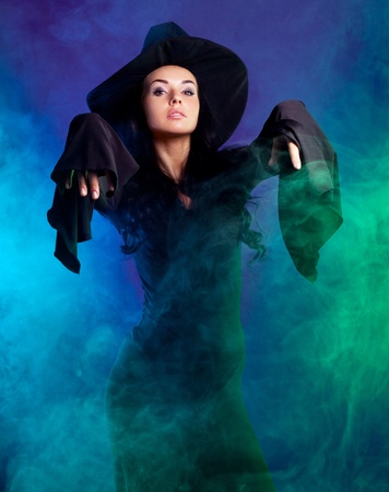 wicked:  sexy young brunette witch with clouds of smoke around her, isolated against white background