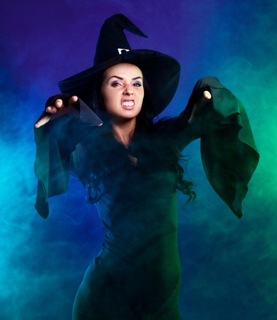 wicked witch: angry brunette witch with clouds of smoke around her, isolated against white background