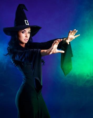 heks: sexy brunette jonge heks met rook om haar heen, zeggen de spell, geïsoleerd tegen witte achtergrond