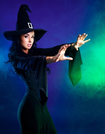 brujas sexis: sexy joven bruja morena con humo alrededor de ella, diciendo que el hechizo, aisladas sobre fondo blanco