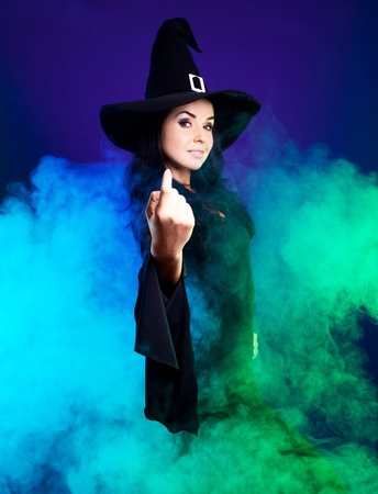 smiling brunette witch with clouds of smoke around her,calling us to come up,  isolated against white background photo